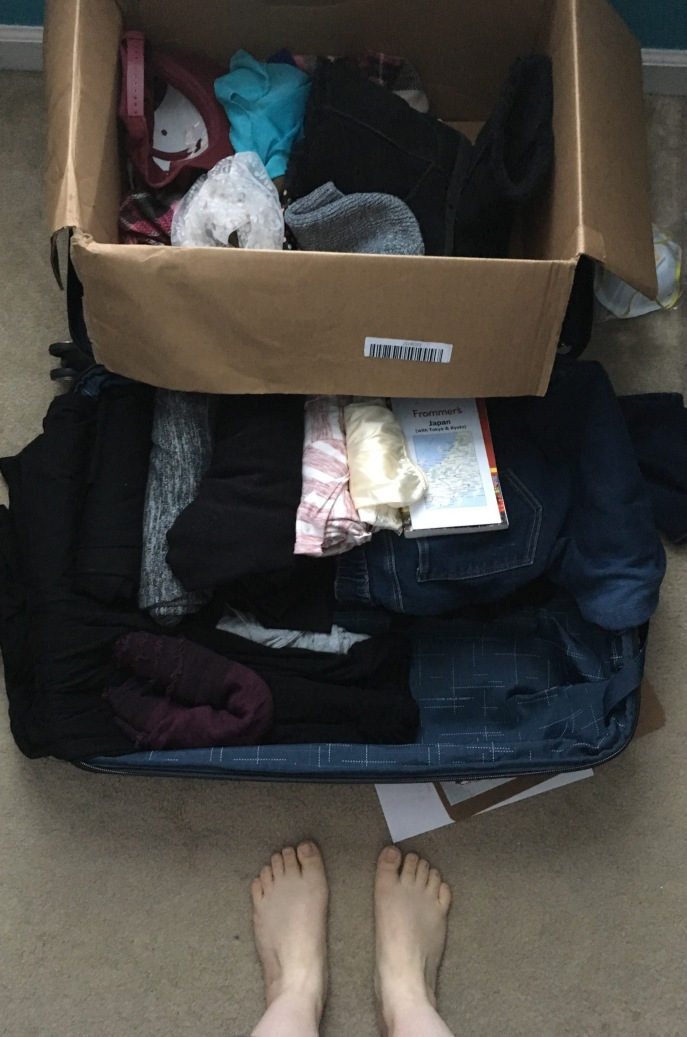 A large suitcase partially packed with clothes, accessories, etc.